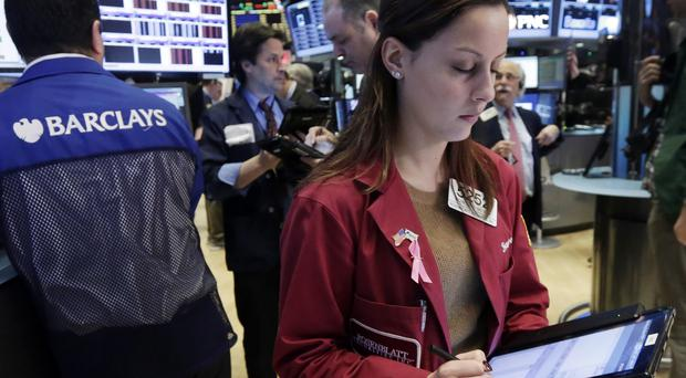 Trader Francesca Grosso works on the floor of the New York Stock Exchange as the market made small gains, led by utilities and telecommunications stocks (AP)