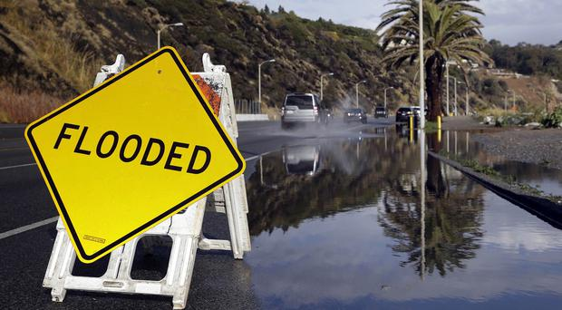 A sign warning of flooded road is posted along the Pacific Coat Highway in Malibu, California (AP)