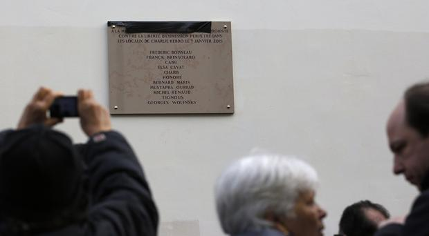 People picture a plaque unveiled earlier by French president Francois Hollande outside satirical newspaper Charlie Hebdo's former office (AP)