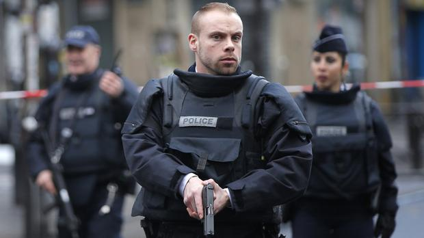 Armed police take up positions after an attempted attack on a police station in Paris (AP)