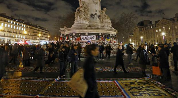 People stand next to a banner reading Je suis Paris (AP)