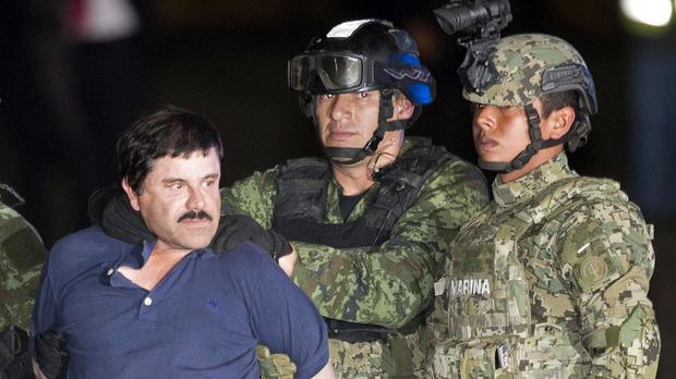 "Joaquin ""El Chapo"" Guzman is escorted to a helicopter in handcuffs by soldiers and marines (AP)"