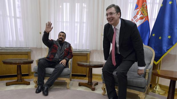 US actor and producer Steven Seagal, left, waves to reporters during a meeting with Serbian Prime Minister Aleksandar Vucic. (AP)