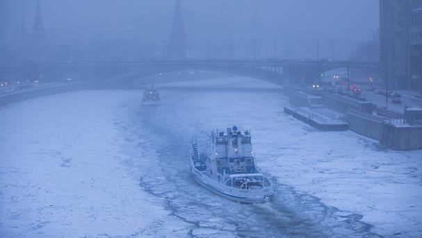 Two ice breakers move along the frozen Moskva River with the Kremlin in the background during snowfall in Moscow (AP)