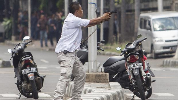 A plainclothes police officer takes aim during a gun battle following the explosions in Jakarta (AP)