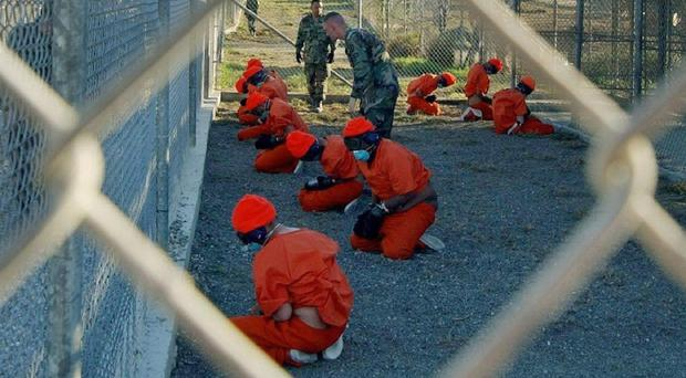 Detainees in orange jumpsuits in a holding area at Guantanamo Bay, Cuba (US Department of Defence/PA)