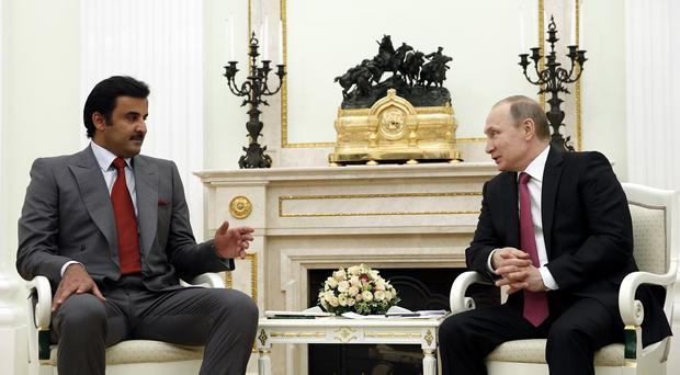 Russian president Vladimir Putin speaks with Qatar's Emir Tamim bin Hamad Al Thani in the Kremlin (AP)