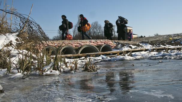 Migrants carry their belongings across a partially frozen stream as they walk from the Macedonian border into Serbia (AP)