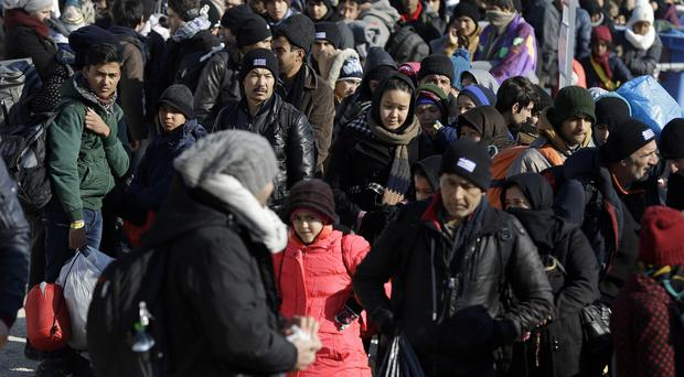 People stand in a queue as Greek police check their documents before crossing the border into southern Macedonia (AP)