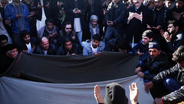 Relatives and friends of a suicide attack victim pray during her burial ceremony in Kabul (AP)