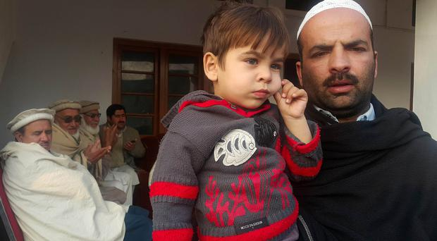 Sajjad Hussain,the brother of Hamid Hussain, holds Hamid's son Hashir Hussain (AP)