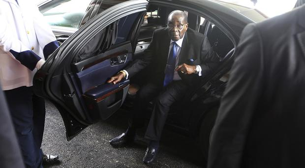 Zimbabwean president Robert Mugabe gets out of his car at State House in Harare after returning from his annual holiday (AP)