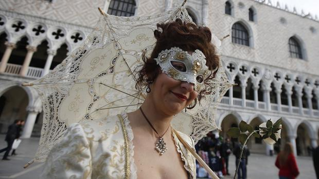 A masked woman walks prior to the Carnival Grand Opening show in Venice, Italy (AP)