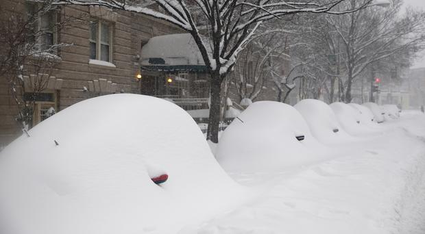 Parked cars are covered by the snow in Washington (AP)