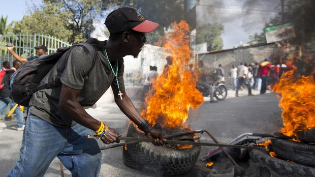 A protester sets tyres alight after it was announced that Haiti's run-off presidential election had been postponed (AP)