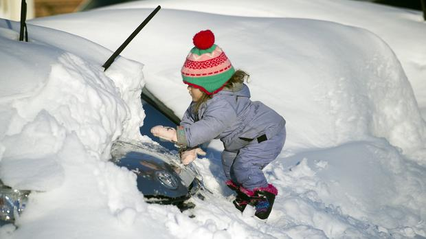 Tess Jorgensson, three, helps her father dig their car out of snow in Virginia (AP)