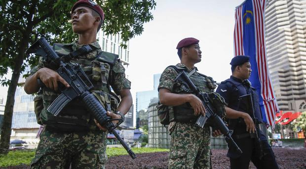 Malaysian military personnel and policeman stand guard outside a shopping centre in Kuala Lumpur (AP)