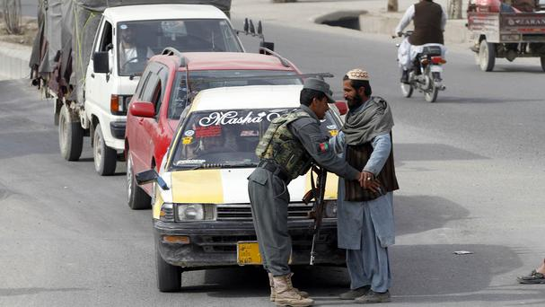 An Afghan policeman searches a passenger at a checkpoint in Kandahar (AP)