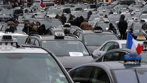 Paris taxi drivers protesting against what they consider unfair competition from rival services (AP)