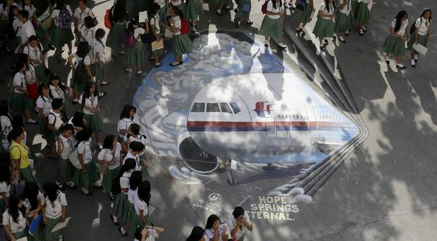 Pupils at Benigno 'Ninoy' Aquino High School with a mural of the missing Malaysia Airlines plane at their campus at Makati city, east of Manila, Philippines (AP)