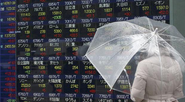 A woman looks at an electronic stock board at a securities firm in Tokyo (AP)
