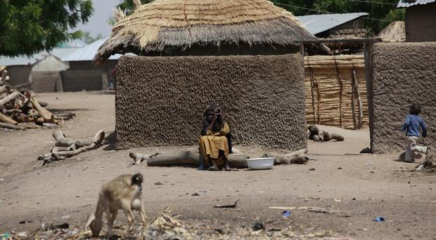 A woman sits outside her home in Chibok, Nigeria (AP)