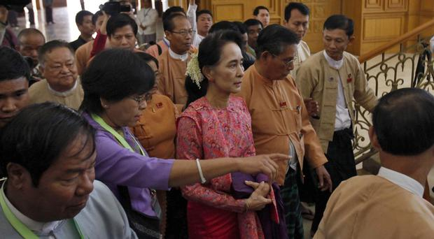 Pro-democracy leader Aung San Suu Kyi, centre, arrives for the inauguration session of Burma's lower house parliament (AP)