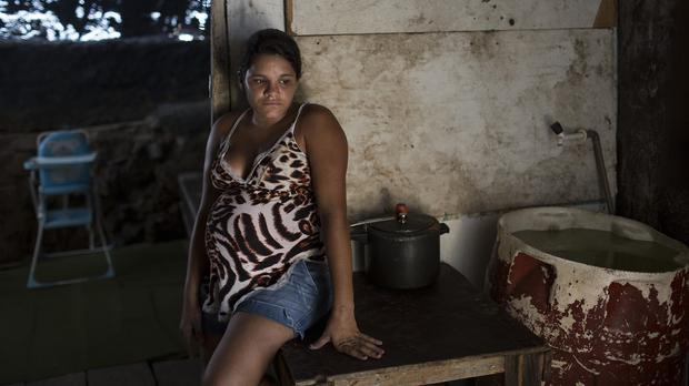 A woman, who is eight months pregnant, rests at a potential mosquito breeding site inside her home. (AP)