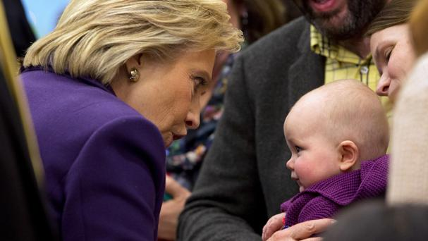 Hillary Clinton greets a baby at a campaign event in New Hampshire (AP)