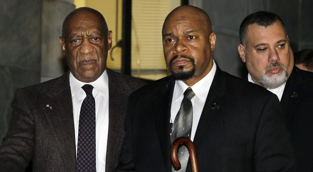 Comedian Bill Cosby, left, is assisted as he leaves after a court appearance in Norristown, Pennsylvania (AP)