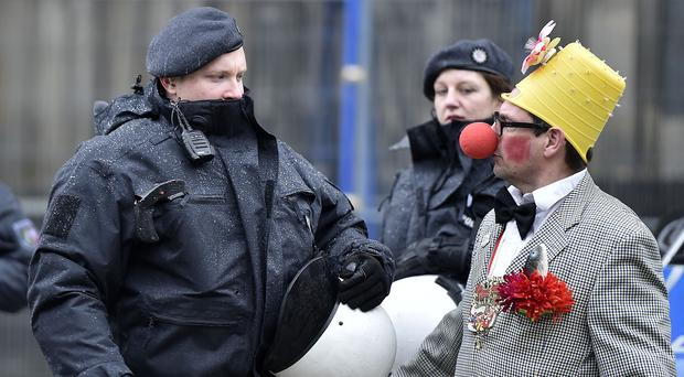 A reveller talks to police during the start of the Cologne Carnival. (AP)