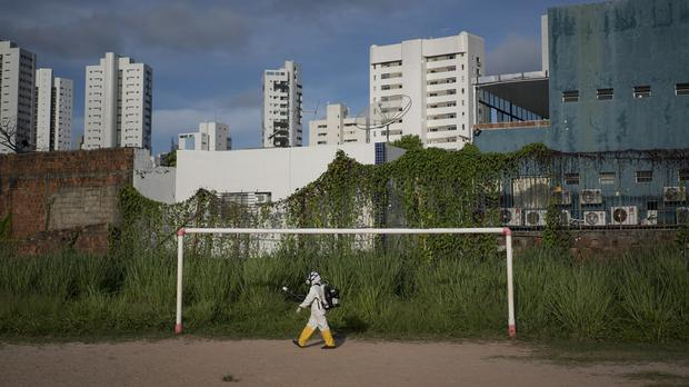A health worker sprays insecticide at a sports centre in Recife, (AP)