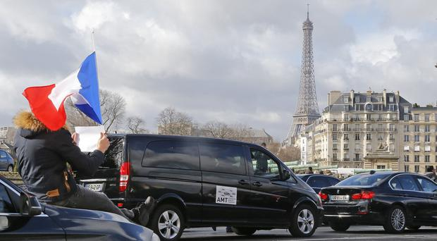 Taxi drivers, one holding the French flag, stage a protest in Paris (AP)