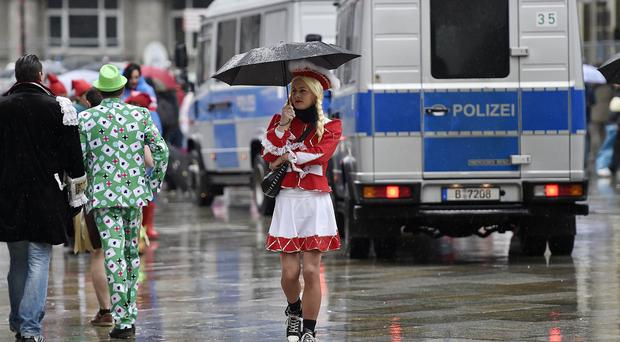 Revellers walk in the rain at the start of the street carnival in Cologne (AP)