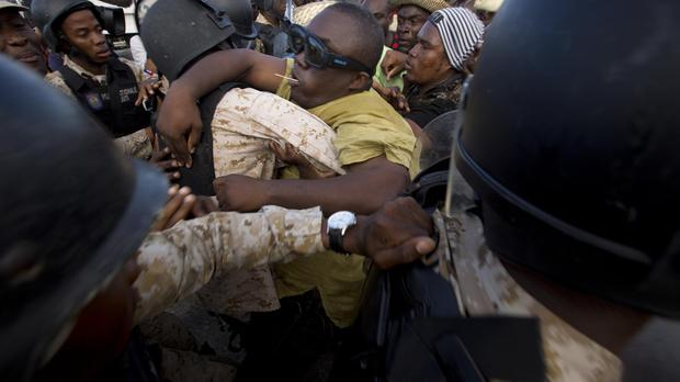 Police officers prevent protesters from getting to the parliament building in Port-au-Prince (AP)