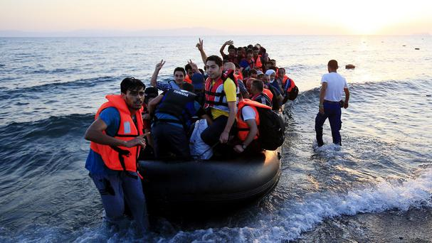 Refugees in a rubber dinghy arrive on the beach at Psalidi near Kos Town, Kos, Greece