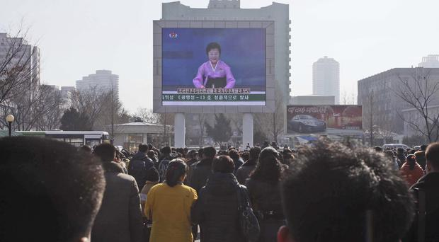 North Koreans watch an electronic screen announcing the launch of a satellite at the Pyongyang Railway Station (AP)