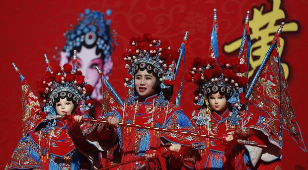 A Chinese dancer in traditional costume performs a cultural dance on stage during a temple fair for a Lunar New Year celebration in Beijing (AP)