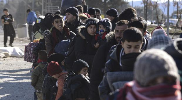 Migrants queue for assistance after arriving in Greece (AP)