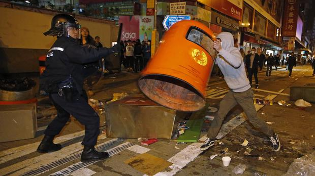 A rioter tries to throw a litter bin at police in Hong Kong's Mong Kok district (AP)