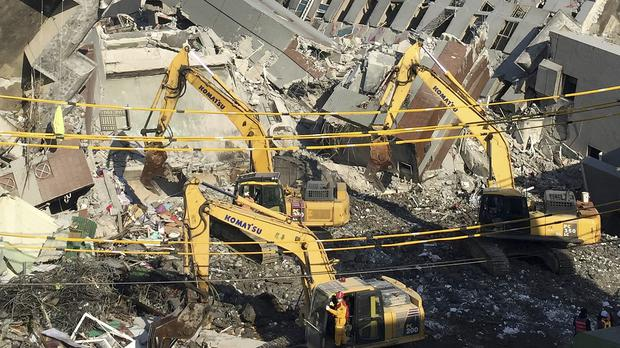 Rescue workers using diggers continue to search the rubble of a collapsed building complex in Tainan, Taiwan (AP)
