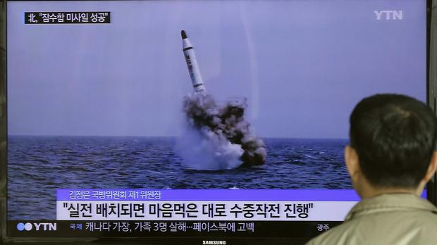 A South Korean man watches a TV news programme showing an image of North Korea's ballistic missile (AP)