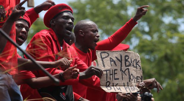 Protesters outside the Constitutional Court in Johannesburg where President Jacob Zuma is appearing (AP)
