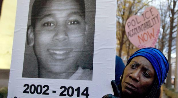 Tomiko Shine holds up a picture of Tamir Rice, the 12-year-old boy fatally shot by a rookie police officer in Cleveland (AP)