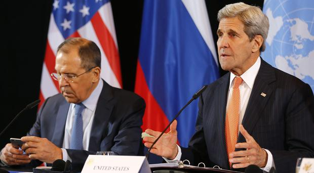 US secretary of state John Kerry, right, and Russian foreign minister Sergey Lavrov reveal the ceasefire agreement after the International Syria Support Group meeting in Munich (AP)
