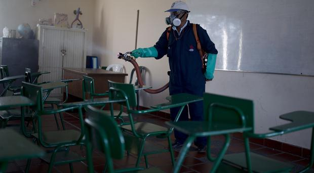 A worker sprays insecticide to kill mosquitoes (AP)