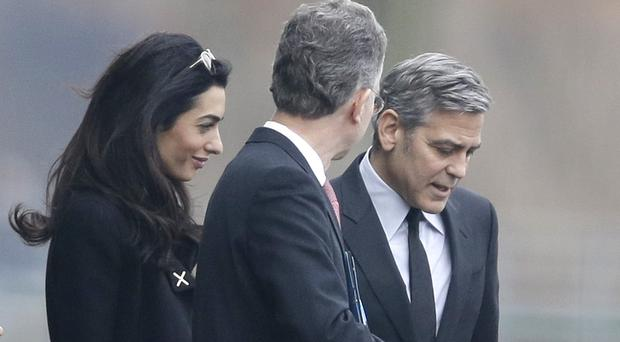 George Clooney and his wife Amal are accompanied by Angela Merkel's foreign policy adviser Christoph Heusgen, centre (AP)