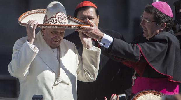 Pope Francis dons a Mexican charro style sombrero that given to him by a person in the crowd, in Mexico City's main square, the Zocalo (AP)