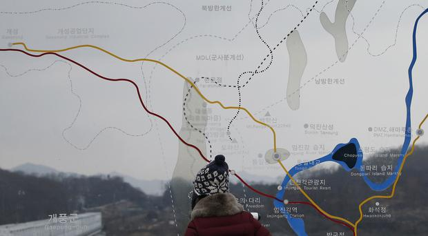 A visitor watches the North side through glass showing a map of the now shut Kaesong industrial park and the border area between North and South Korea (AP)