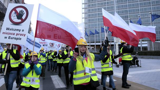 Polish steel workers wave flags as they participate in a demonstration around the European quarter of Brussels (AP)